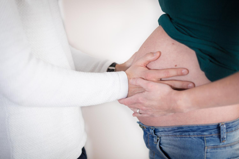 Zwangerschapsshoot van een blote buik met de handen van de man